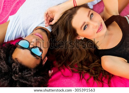 Close up summer portrait of cheerful young couple rest un the summer beach. Bright sunny colors . Beautiful stylish girl and her handsome man lying on mat. Wearing sunglasses . #305391563