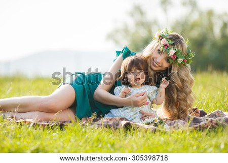 young mother playing with baby girl outdoors in summer park. Mother and baby. woman with daughter having fun together. Mother and baby in park portrait #305398718