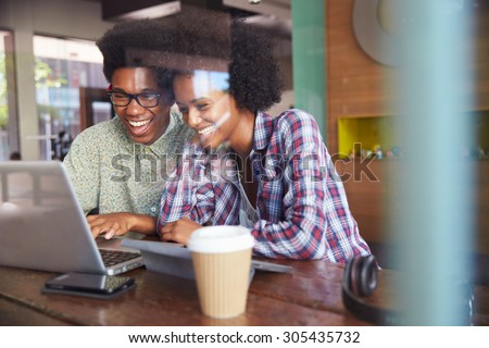 Two Young Businesspeople Working On Laptop In Coffee Shop