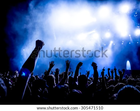 silhouettes of concert crowd in front of bright stage lights - a small depth of field signifies that the focused area is narrow #305471510
