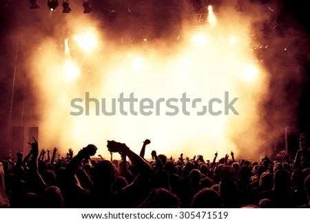 silhouettes of concert crowd in front of bright stage lights - a small depth of field signifies that the focused area is narrow #305471519