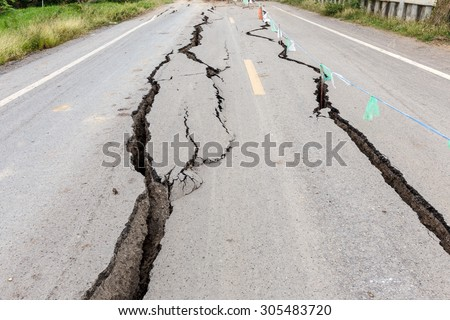Asphalt road cracked and broken from earthquake. Royalty-Free Stock Photo #305483720