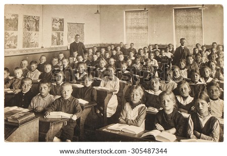 Retro picture of classmates. Group of children in the classroom. Vintage photo from 1920 with original film grain, blur and scratches.
