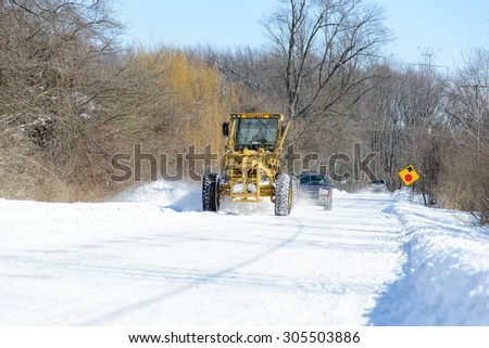 CHINA, MI, USA / FEBRUARY 18, 2014: After a snow fall in China, MI a St Clair County Road Commission road grader clears the road on February 18, 2014. #305503886