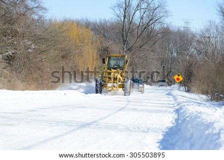 CHINA, MI, USA / FEBRUARY 18, 2014: After a snow fall in China, MI a St Clair County Road Commission road grader clears the road on February 18, 2014. #305503895