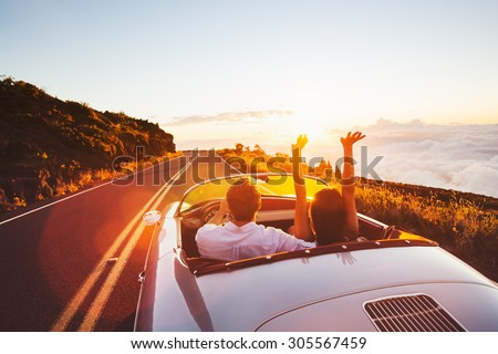 Happy Couple Driving on Country Road into the Sunset in Classic Vintage Sports Car  Royalty-Free Stock Photo #305567459