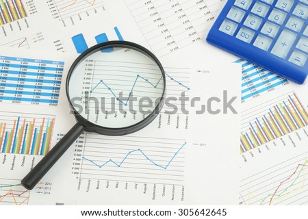 Business concept, calculator and magnifying glass on financial charts and graphs #305642645