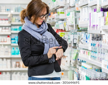 Mid adult female consumer in casuals using smartwatch in pharmacy #305644691