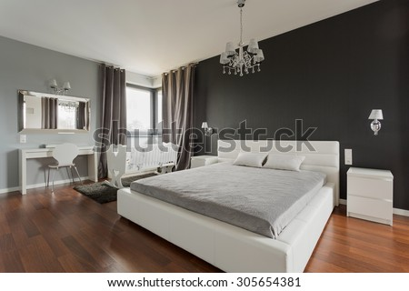 Big comfortable double bed in elegant classic bedroom #305654381