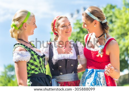 Women friends visiting Bavarian fair in national costume or Dirndl  #305888099