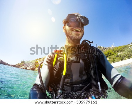 Smiling scuba diver portrait at the sea shore. Diving goggles on. Royalty-Free Stock Photo #305979161