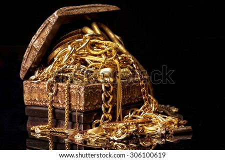 Old wooden chest with pile of various golden jewelry, isolated against black background. #306100619