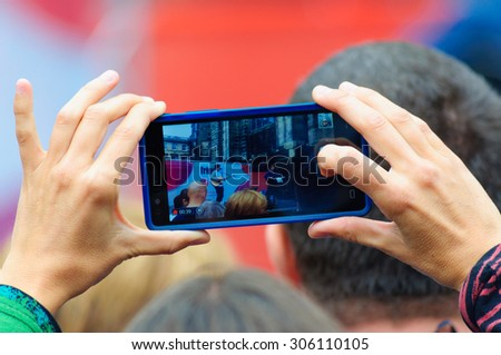 EDINBURGH, SCOTLAND - AUGUST 8, 2015: Hands holding a mobile phone recording a performance on the Royal Mile during the Edinburgh International Fringe Festival #306110105