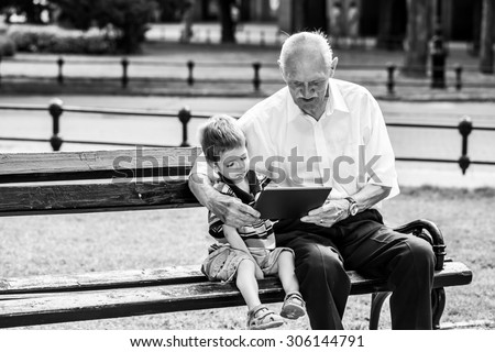 Grandchild teaching to his grandfather to use tablet on a bench. Black and white photography #306144791