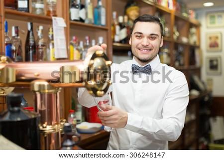 Modern bar with bottles at background and happy smiling male bartender  #306248147