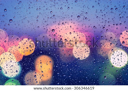 Drops of rain on window with abstract bokeh background