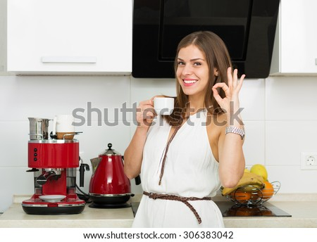 Beautiful woman making coffee for breakfast in the kitchen #306383042