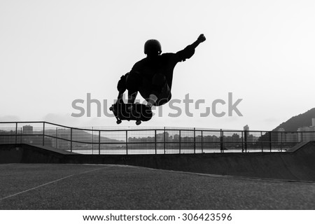skateboarder jumping in a bowl of a skate park