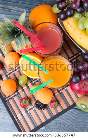 Breakfast concept with orange and strawberry juice, coffee, fruits on wooden table #306557747