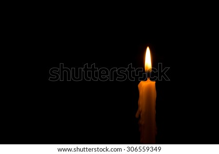 One light candle burning brightly in the black background #306559349