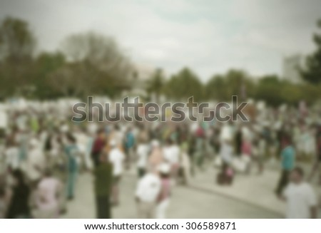 Background blur of crowd at political rally in the United States holding signs and carrying US flags for upcoming election cycle in 2016 presidential campaigns. Copy space. Vintage filter added.