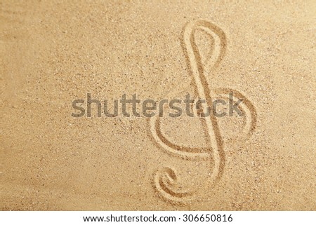 Violin key drawn on a beach sand