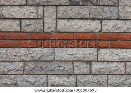Gray stone wall with a slim red brick line. #306807695