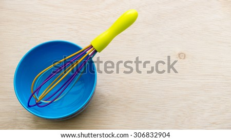 Colourful cute plastic whisk or egg beater and blue bowl on empty wooden surface. Concept of kitchen tool for kids or young chef. Slightly de-focused and close-up shot. Copy space. #306832904