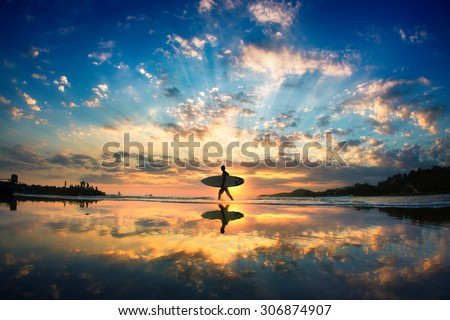 Sun surfer. A man is walking with a surf in his hands across the sea shore.  Royalty-Free Stock Photo #306874907