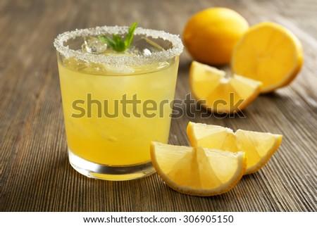 Glass of lemon juice on wooden table, closeup #306905150
