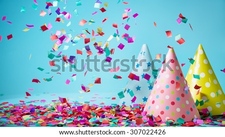 Colored confetti and party hat on blue background Royalty-Free Stock Photo #307022426