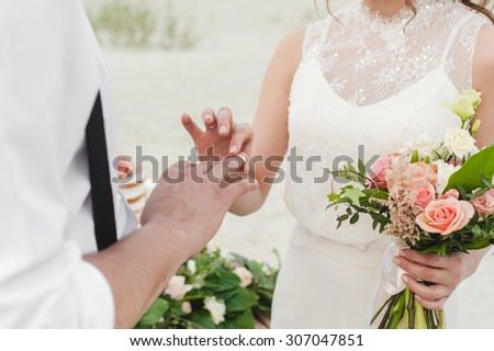 Bride wears the ring on the finger of the groom #307047851