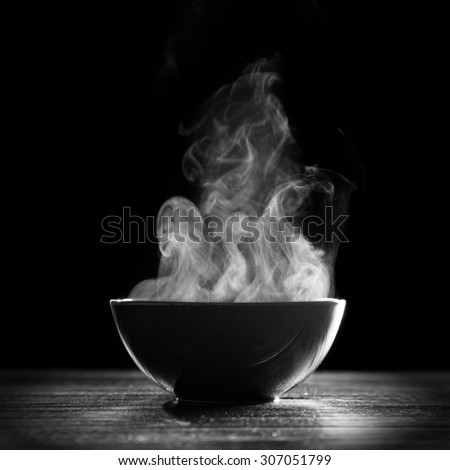Bowl of hot soup on black background #307051799