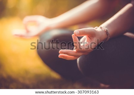 Yoga meditation in park, healthy female in peace, soul and mind zen balance concept. Selective focus and shallow DOF. Toned picture