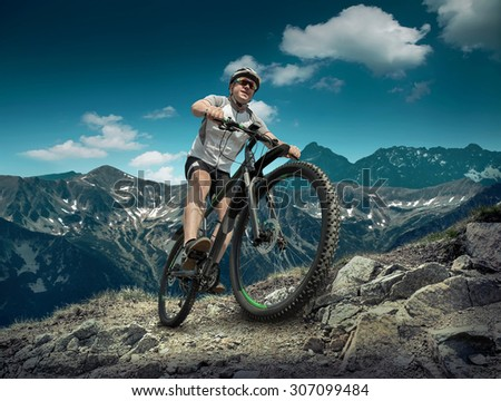 Man in helmet and glasses stay on the bicycle under sky with clouds. #307099484