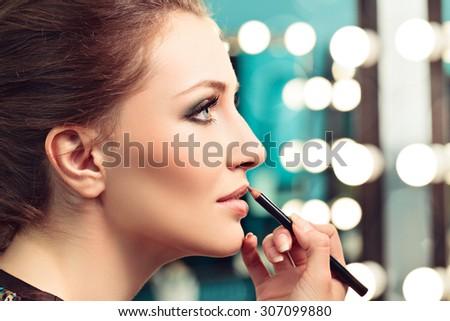 Make-up artist applying lip liner on model's lips, focus on model's eye #307099880