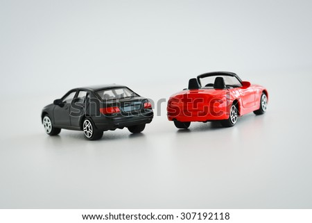 Black and red toy cars on white background suggesting a competition