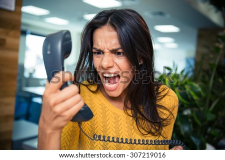 Angry businesswoman shouting on phone in office Royalty-Free Stock Photo #307219016