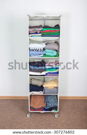 clothes nicely arranged on a shelf. Tidy wardrobe with colorful clothes and accessories against the wall #307276802