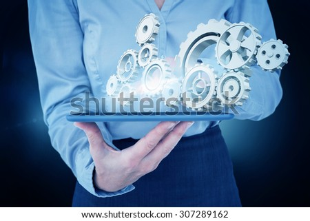Businesswoman using her tablet against blue background with vignette #307289162
