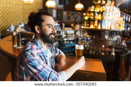 people, drinks, alcohol and leisure concept - happy young man drinking beer at bar or pub #307340285
