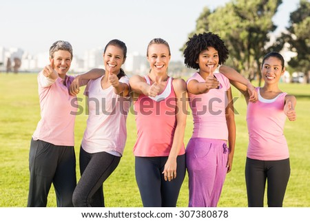 Portrait of smiling women wearing pink for breast cancer and doing thumbs up in parkland #307380878