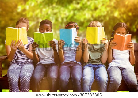 Children reading books at park against trees and meadow in the park