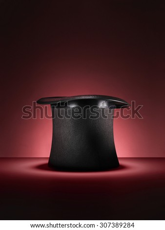 Shot of a traditional magicians style top hat set up for a trick or illusion on a red background with space left for the designer to add an object or type.  #307389284