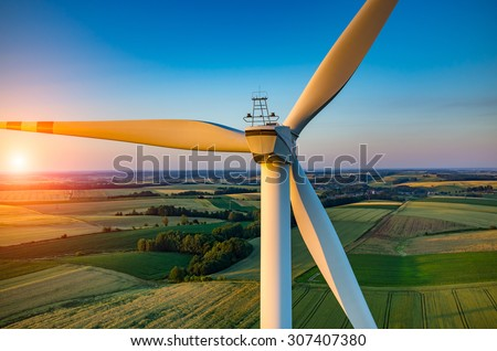 Beautiful sunset above the windmills on the field #307407380