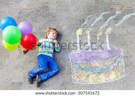 Happy little kid boy having fun with big birthday cake picture drawing with colorful chalks and balloons. Creative leisure for children outdoors in summer.