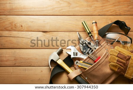 tools in tool belt on wood planks with copy space Royalty-Free Stock Photo #307944350