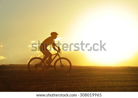 profile silhouette of sport man cycling uphill riding cross country mountain bike on sunset field with harsh sun light and high contrast in amazing beautiful rural landscape with lens flare #308019965