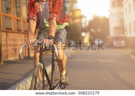 Close up hipster on bike in the city at sunset. Shot with sunflare and without face. #308225579