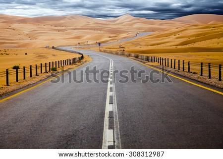 Winding black asphalt road through the sand dunes of Liwa oasis, United Arab Emirates #308312987